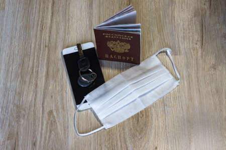 medical mask and keys, medical mask and phone on the table, white medical mask and passport