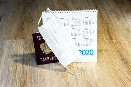 white medical mask and calendar for 2020, medical mask and passport on the table (January, February, May, December)