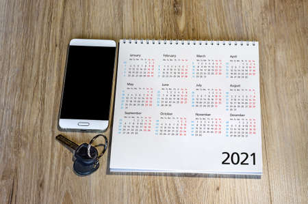 calendar for 2021 and keys on the table, white smartphone and calendar for 2021 (January, February, may, December)