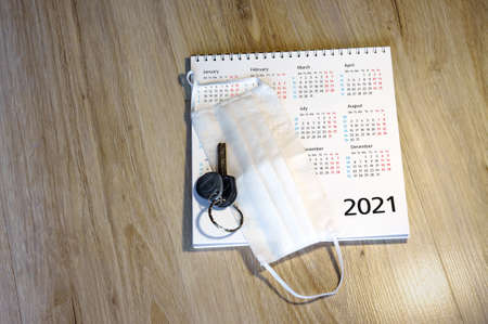 white medical mask and calendar for 2021 (January, February, may, December), medical mask and keys on the table