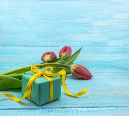A gift and tulips on a wooden background. Spring flowers and a gift box. Red tulips and green packaging.
