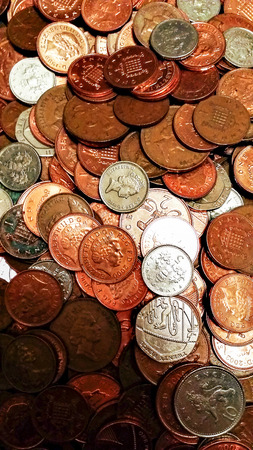 pence: Closeup image of a pile of british coins rangin from one penny to 20 pence pieces.