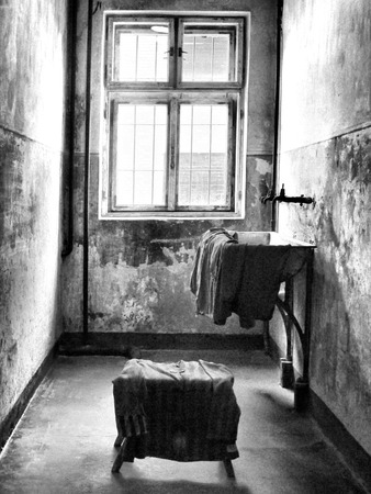 pealing: Black and white image of the interior of a prisoncell. The room contains a single window, a sink, and a stool. Stock Photo