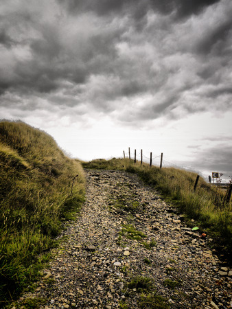 moody: A gravel path leading up to a moody sky.
