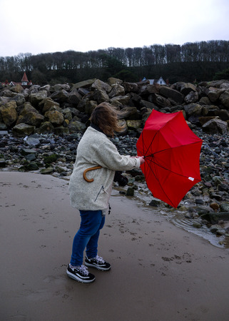 turned out: Woman trying to keep hold of an umbrella that has turned inside out in the wind,