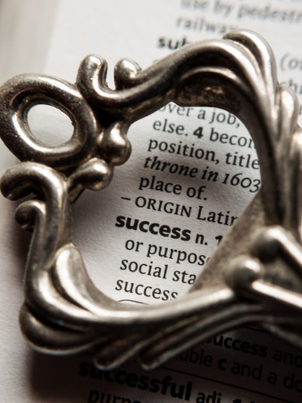 Conceptual image of the dictionary definition of success surrounded by the top half of a vintage key.