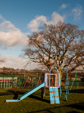 climbing frame: An empty park containing a slide, swings and climbing frame. Stock Photo