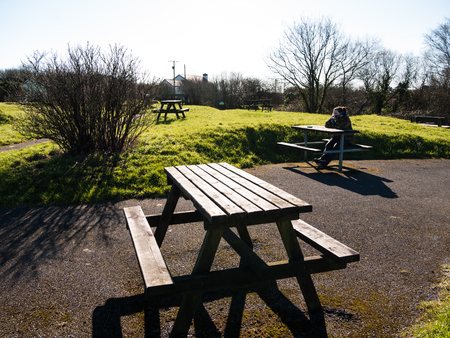seating area: A young woman sitting at a picnic bench alone in an empty seating area.