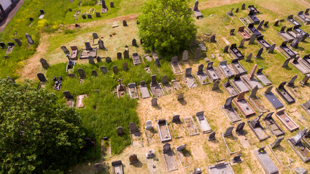 solemn land: An aerial view of an old, run down graveyard with patchy grass.
