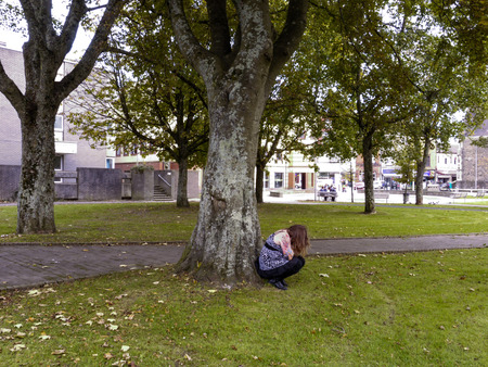 crouched: A young woman crouched by a tree looking distressed and upset.