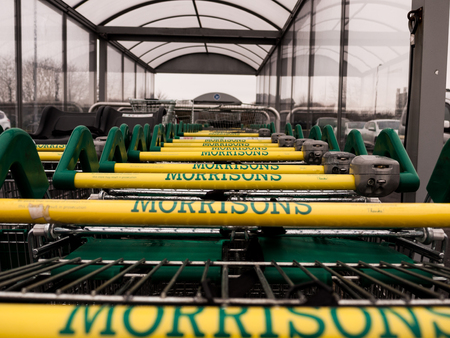 A row of Morrisons trolleys in an outdoor trolley bay.