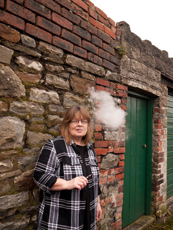 smoking pipe: A mature woman smokes an electronic cigarette outside in poor weather conditions Stock Photo