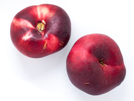Two Nectarines sit on a white background