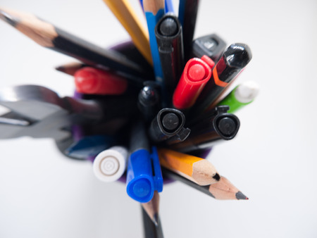 A pot containing stationary items such as pens and pencils,