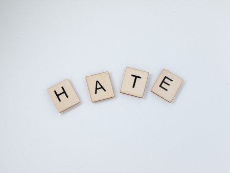 The word Hate spelled out with wooden letter tiles.
