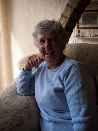 A single senior woman displays happiness by laughing. Stock Photo