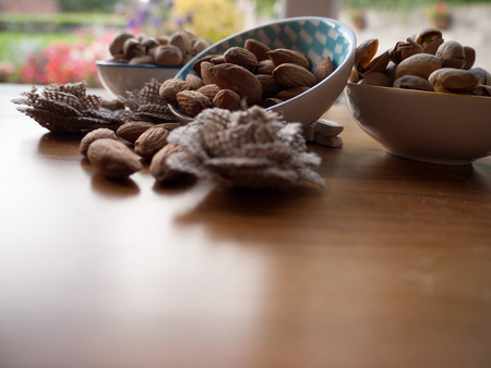 Three bowls containing pistachio and almond nuts on a wooden surface