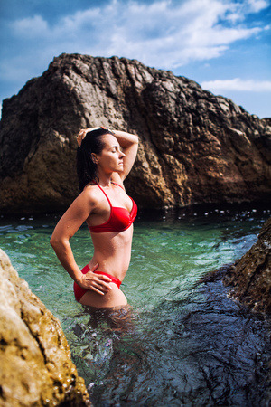 Girl in a red bathing suit on a stony beach