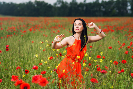 The girl in the red dress in the field of poppies
