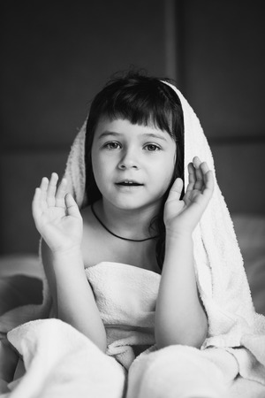 bedchamber: Washed the girl in a towel sitting on a white bed