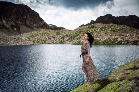 Girl in colorful dress on a shore of a clear mountain lake