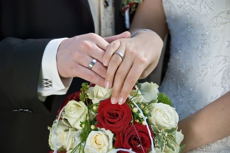 the bride and the groom showing their rings above the brides bouqet photo