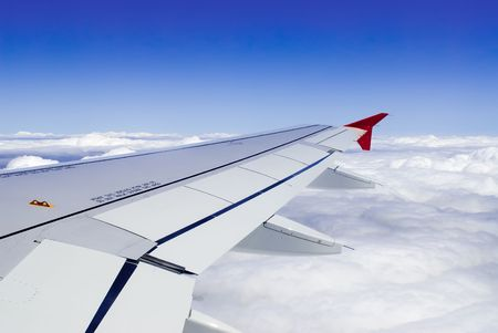 a view though an airplane window where one can see the wing and beautiful cloudy sky