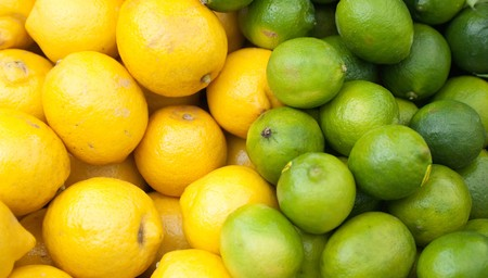 lime fruit:  lemons and limes stacked up for sale on a market