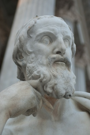 a sculpture of a thinking philosopher with a pencil in his hand photo
