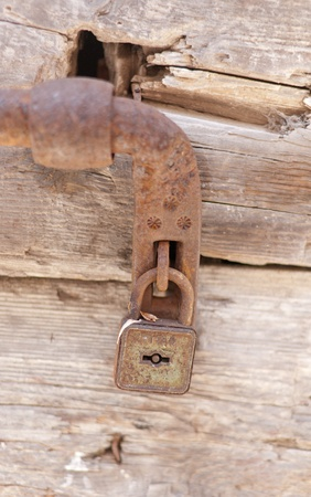 a rusty lock on a wooden door photo