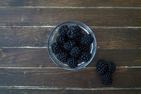 blackberries on transparent bowl on a wooden table seen from above