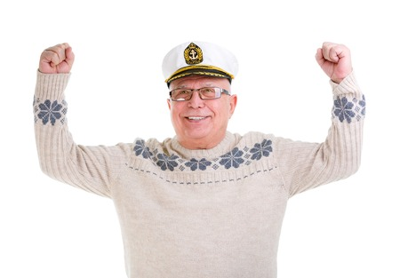 Closeup portrait of happy old senior man with a smile and white teeth,  raised his hands up, boat captain cap, isolated on white background photo