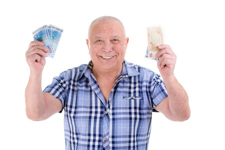 financial reward: Closeup portrait, happy, excited successful senior lucky elderly man holding money euros banknotes in hands isolated white background. Positive emotion facial expression feeling. Financial reward savings