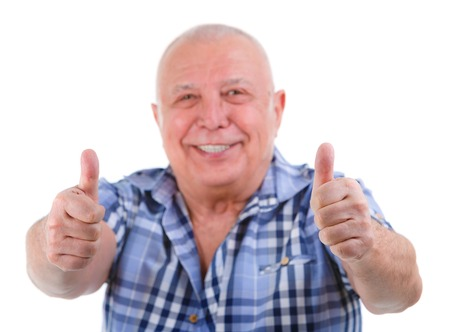 two thumbs up: Closeup portrait, Happy smiling old man with white teeth, shows gesture two thumbs up on white. Focus on fingers, face blurred. Isolated