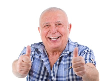two thumbs up: Closeup portrait of Happy smiling senior with white teeth, shows gesture two thumbs up. Focus on face, fingers blurred. Isolated on white