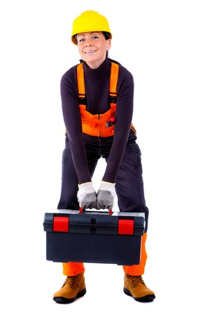 servicewoman: Young Servicewoman wearing yellow helmet and blue overall, holding a heavy tool box, Isolated on white background Stock Photo