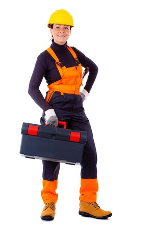 overall: Happy Servicewoman wearing yellow helmet and blue overall, holding black toolbox, Isolated on white background