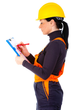 servicewoman: Young of Servicewoman builder wearing yellow helmet and blue overall, writing something on building plan isolated on white background Stock Photo