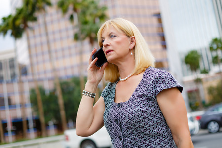 55 years old: Attractive business woman 65 years in the downtown calling with mobile phone, Lifestyle woman on phone, Business concept - businesswoman talking on the phone in street