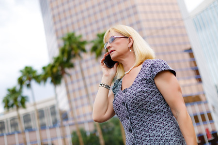 55 years old: Close Up portrait Serious attractive business woman in glasses 65 years in the downtown talking with mobile phone, Lifestyle woman on phone, Business concept - businesswoman calling on the phone in street
