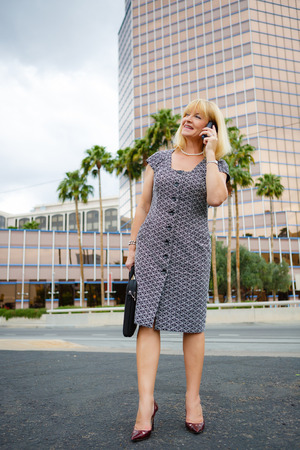 45 years old: Happy and smiling Old business woman 60-65 years in the downtown talking with mobile phone, Lifestyle woman on phone and shoes hills Stock Photo