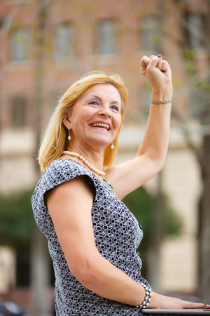 65 years old: Close Up portrait, Happy and Smiling old senior woman 60-65 years, looking to up, with gesture on face and raised hand up with fist in New York city park