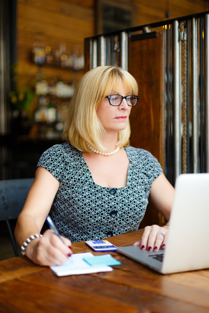 55 years old: Old senior blonde business woman in the glasses sitting at a cafe city with a laptop and calculator, writes notes
