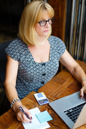 55 years old: Old senior blonde business woman 60-65 years in the glasses sitting at a cafe city with a laptop and calculator, writes notes