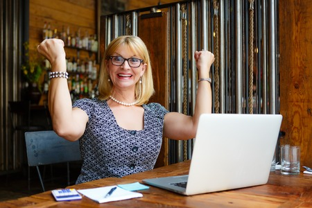55 years old: Close Up portrait Smiling old senior blonde business woman in the glasses, alone with laptop in summer cafe with gesture on face and raised hands up with fists