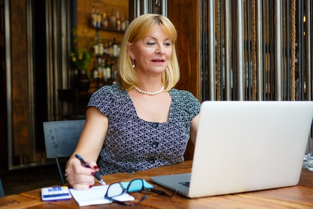 65 years old: Smiling old senior blonde business woman 60-65 years, alone with laptop in summer cafe