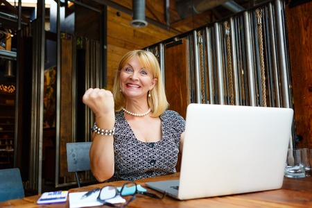 65 years old: Smiling old senior blonde business woman 60-65 years, alone with laptop in summer cafe with gesture on face and raised hand up with fist Stock Photo