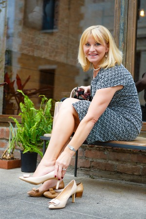 Happy old senior blonde woman 60-65 years, sitting on bench in downtown city put high heel shoes on her feet