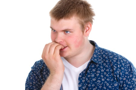 psychotic: Closeup portrait of nervous stressed young nerdy guy man biting fingernails looking anxiously craving something isolated on white background. Negative emotion expression feeling Stock Photo