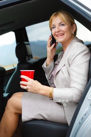 donna ricca: Felice e sorriso Donna maggiore anziana 6065 anni con i denti bianchi parlando da cellulare mobile nel retro di una macchina e tenendo il bicchiere di plastica in mano. Archivio Fotografico
